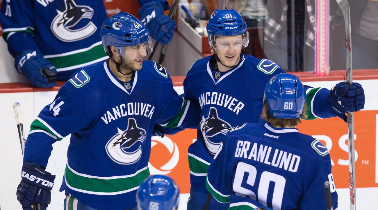 Vancouver Canucks' Matt Bartkowski, left, Jared McCann, top right, and Markus Granland, of Finland, celebrate McCann's goal against the Los Angeles Kings during the second period of an NHL hockey game in Vancouver, British Columbia, Monday, April 4, 2016.