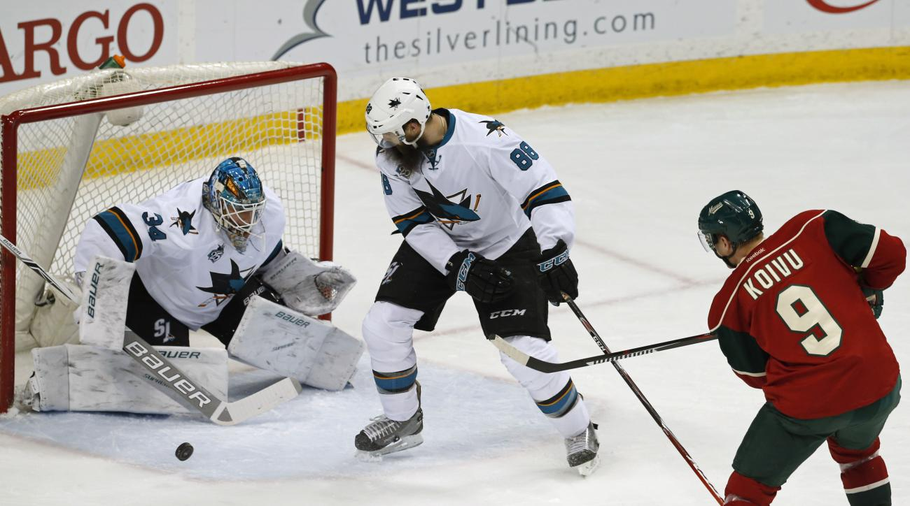 San Jose Sharks goalie James Reimer, left, stops a shot by Minnesota Wild's Mikko Koivu of Finland in the first period of an NHL hockey game Tuesday, April 5, 2016, in St. Paul, Minn. (AP Photo/Jim Mone)