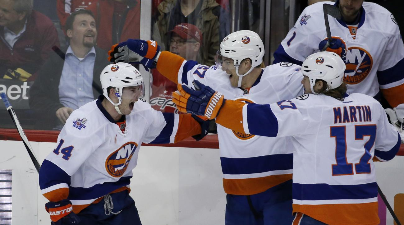 New York Islanders defenseman Thomas Hickey (14) celebrates his game-winning goal with center Anders Lee (27) and left wing Matt Martin (17) after an NHL hockey game against the Washington Capitals, Tuesday, April 5, 2016, in Washington. The Islanders won