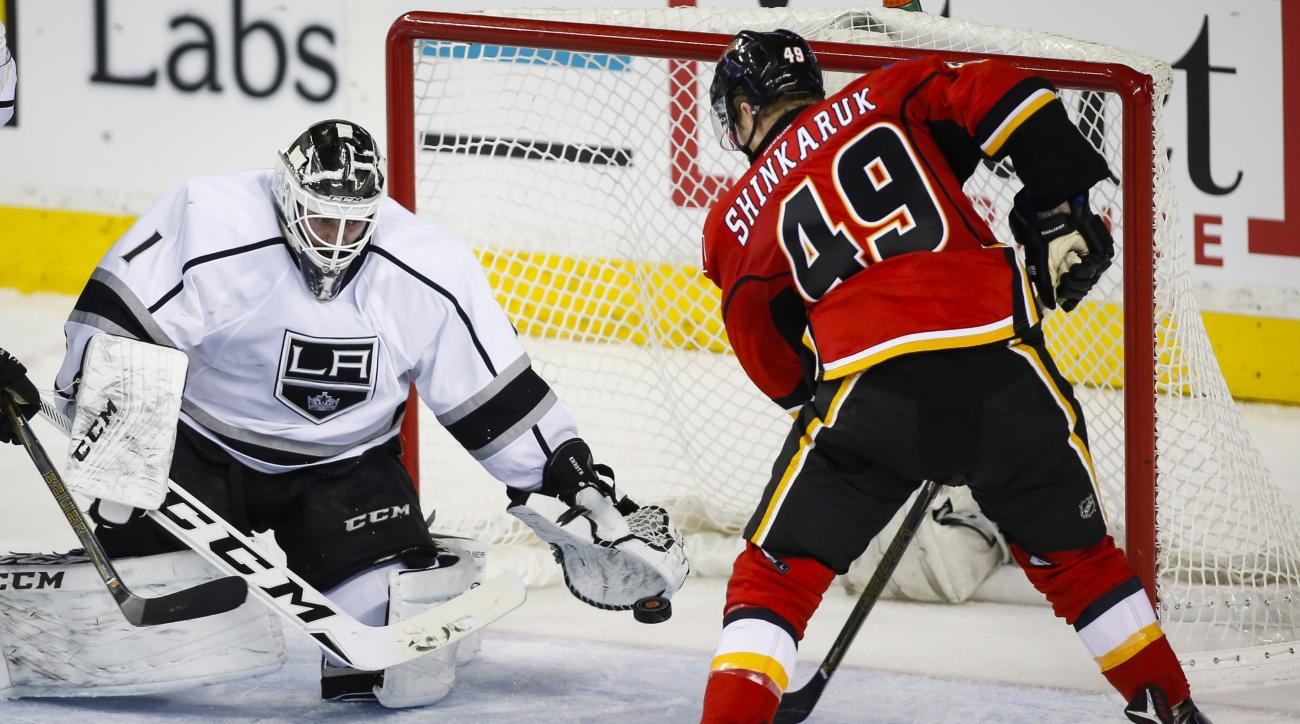 Los Angeles Kings goalie Jhonas Enroth, left, of Sweden, can't stop a shot from Calgary Flames' Hunter Shinkaruk during the second period of an NHL hockey game, Tuesday, April 5, 2016 in Calgary, Alberta.  (Jeff McIntosh/The Canadian Press via AP) MANDATO