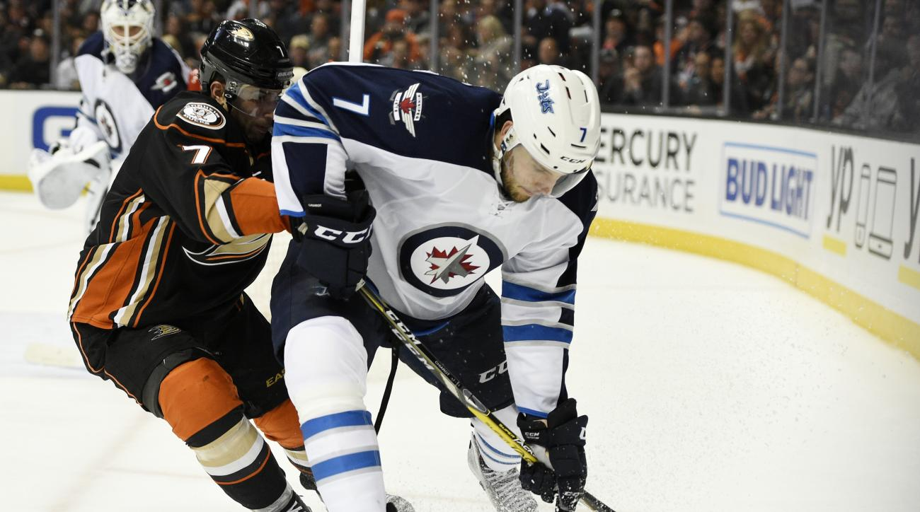 Winnipeg Jets defenseman Ben Chiarot, right, moves the puck while under pressure drom Anaheim Ducks left wing Andrew Cogliano, left, during the second period of an NHL hockey game in Anaheim, Calif., Tuesday, April 5, 2016. (AP Photo/Kelvin Kuo)