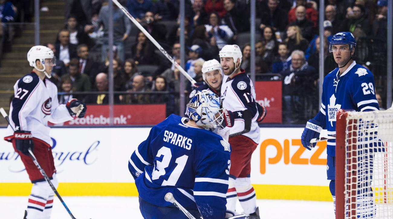 Toronto Maple Leafs goalie Garret Sparks (31) looks on as Columbus Blue Jackets' Brandon Dubinsky (17) celebrates his goal with teammates during the third period of an NHL hockey game, Wednesday,  April 6, 2016 in Toronto.  (Nathan Denette/The Canadian Pr