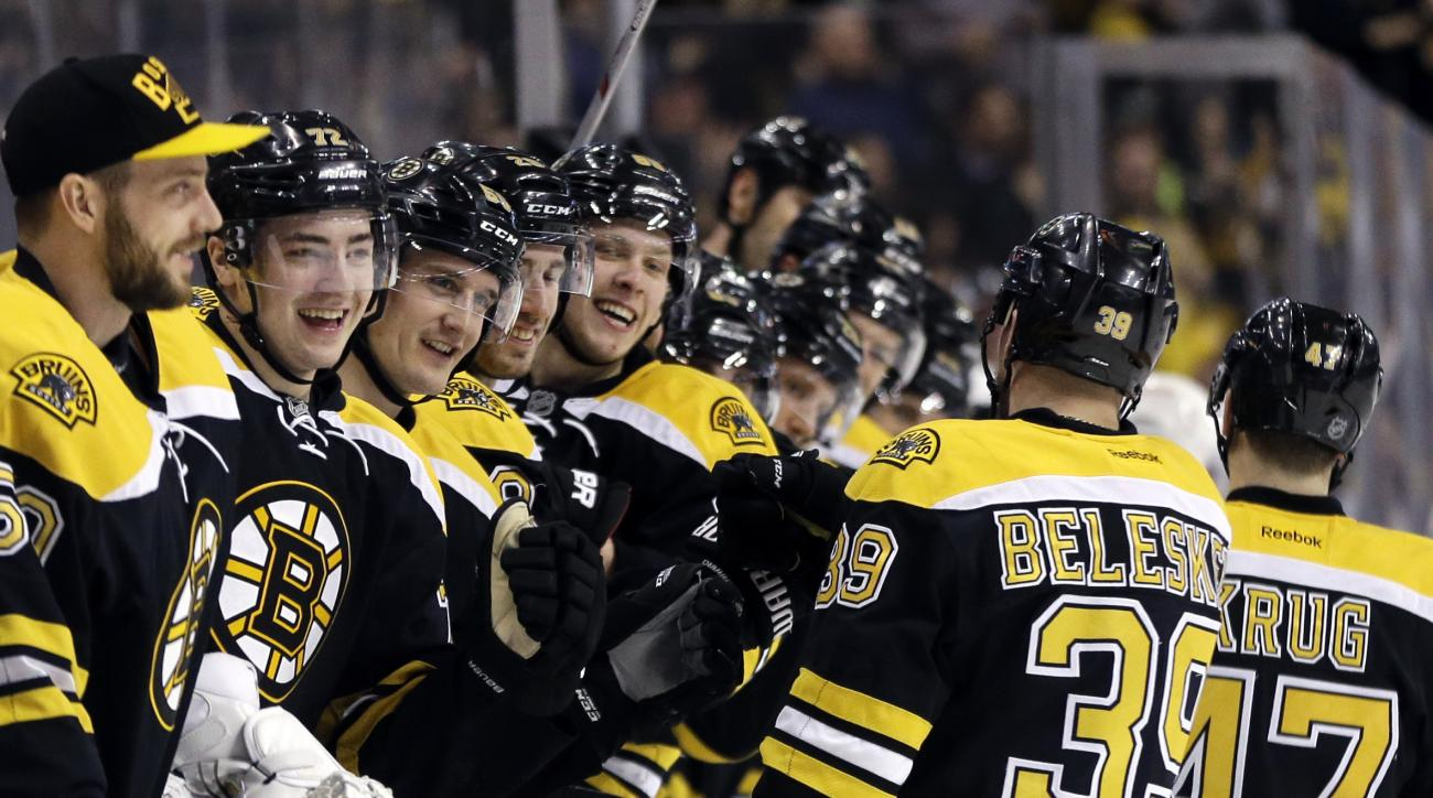 The Boston Bruins bench greets Bruins defenseman Torey Krug (47) and left wing Matt Beleskey (39) after Krug's goal against the Detroit Red Wings in the second period of an NHL hockey game, Thursday, April 7, 2016, in Boston. (AP Photo/Elise Amendola)