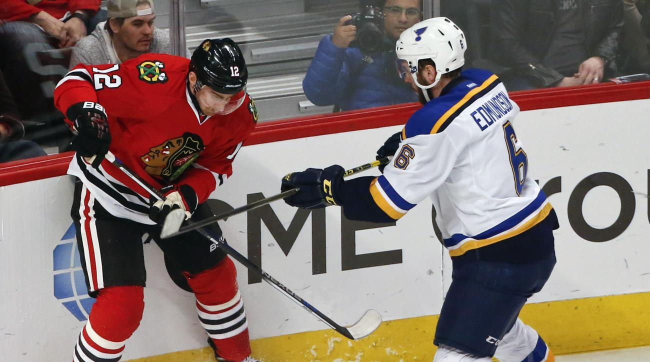 Chicago Blackhawks left wing Tomas Fleischmann (12) fights for the puck with St. Louis Blues defenseman Joel Edmundson (6) during the first period of an NHL hockey game Thursday, April 7, 2016, in Chicago. (AP Photo/Kamil Krzaczynski)