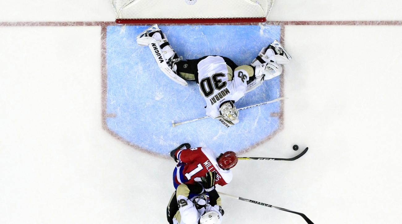 Washington Capitals right wing Justin Williams (14) cannot get the puck past Pittsburgh Penguins goalie Matt Murray (30) as Pittsburgh Penguins defenseman Kris Letang (58) defends in the overtime period of an NHL hockey game, Thursday, April 7, 2016, in W