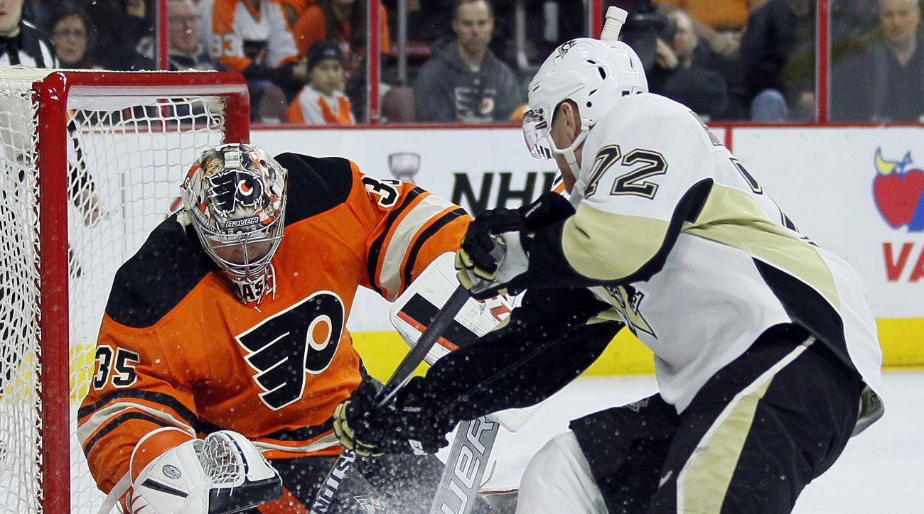 Philadelphia Flyers' Steve Mason, left, defends as Pittsburgh Penguins' Patric Hornqvist, right, attacks during the first period of an NHL hockey game Saturday, April 9, 2016, in Philadelphia. (AP Photo/Tom Mihalek)