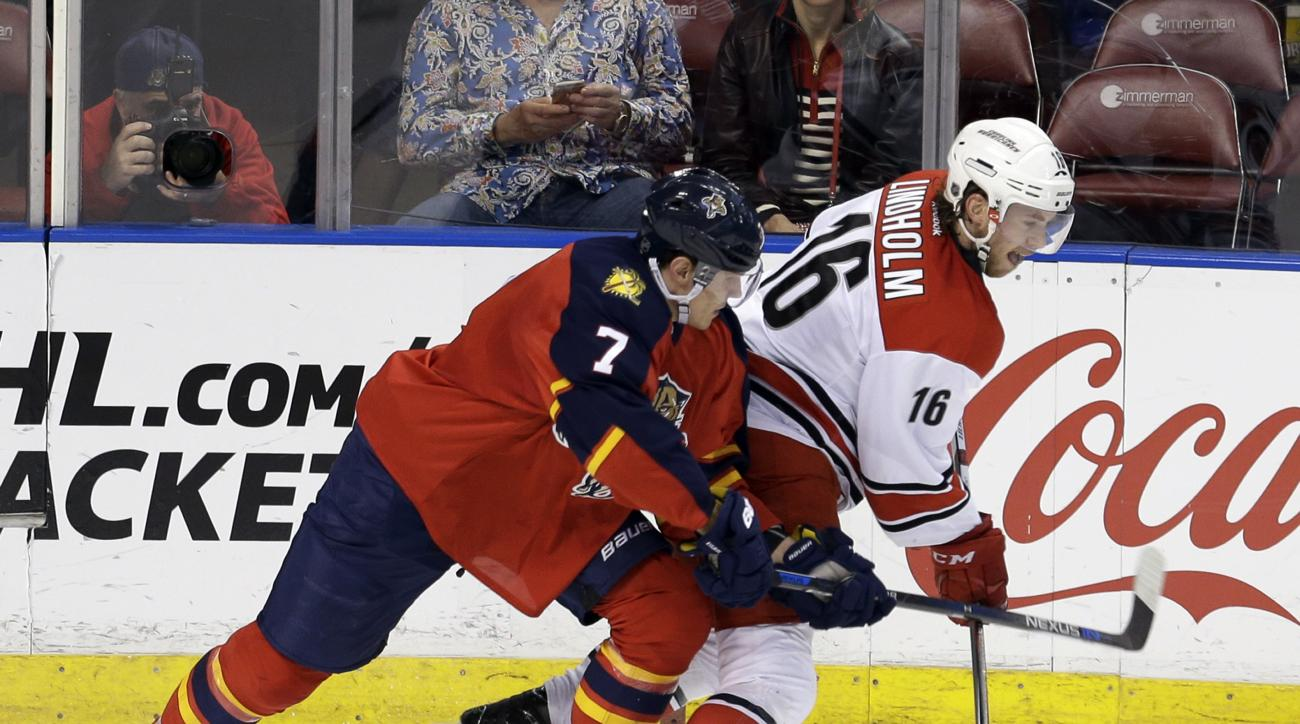 Carolina Hurricanes center Elias Lindholm (16) is checked by Florida Panthers defenseman Dmitry Kulikov (7) during the second period of an NHL hockey game, Saturday, April 9, 2016, in Sunrise, Fla. (AP Photo/Alan Diaz)