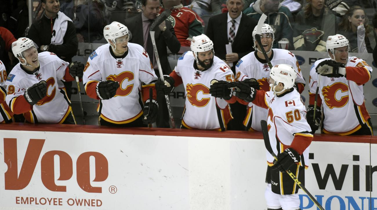 The Calgary Flames congratulate teammate Patrick Sieloff (50) after scoring against the Minnesota Wild during the third period of an NHL hockey game Saturday, April 9, 2016, in St. Paul, Minn. The Flames won 2-1. (AP Photo/Hannah Foslien)