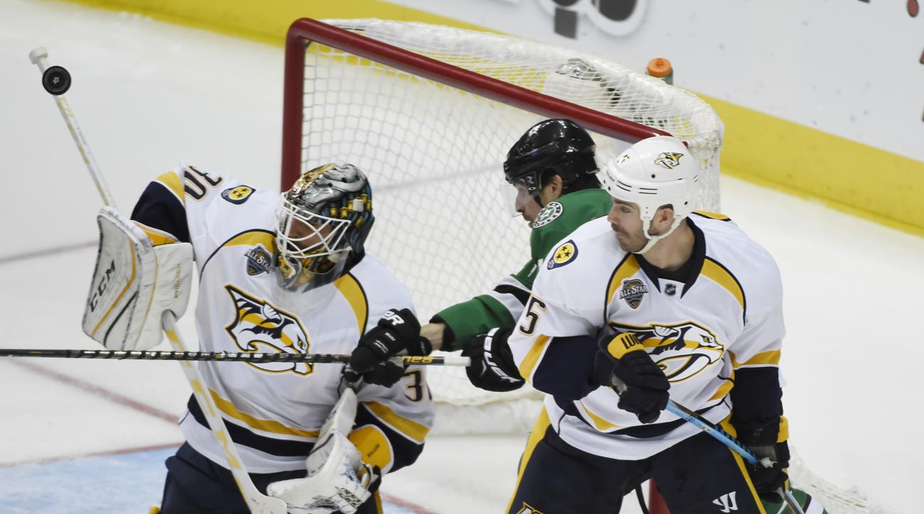Nashville Predators goalie Carter Hutton (30) blocks a shot as Dallas Stars left wing Patrick Sharp (10) and Nashville Predators defenseman Barret Jackman (5) crowd the goal during the second period of an NHL hockey game on Saturday, April 9, 2016, in Dal