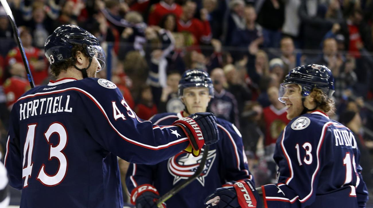Columbus Blue Jackets' Scott Hartnell, left, celebrates his game-winning goal against the Chicago Blackhawks withteammates Cam Atkinson, left, and Alexander Wennberg, of Sweden, during the overtime period of an NHL hockey game Saturday, April 9, 2016, in