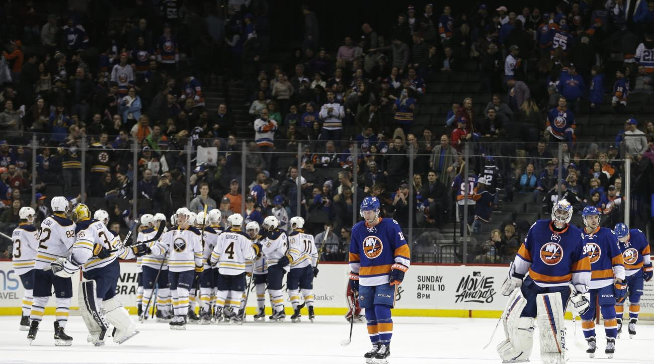 New York Islanders goalie Christopher Gibson, right front, leaves the ice with his teammates as the Buffalo Sabres celebrate after an NHL hockey game Saturday, April 9, 2016, in New York. The Sabres won 4-3 in overtime. (AP Photo/Frank Franklin II)