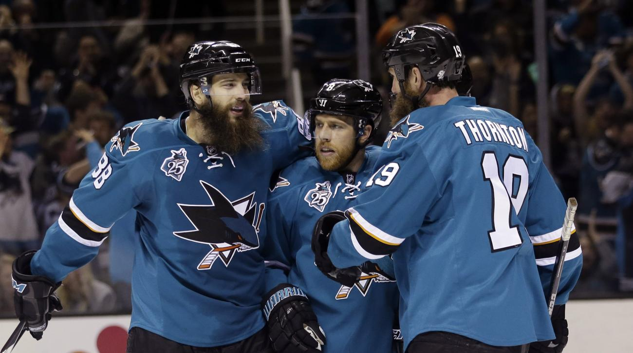 San Jose Sharks' Joe Pavelski, center, celebrates after scoring with teammates Brent Burns, left, and Joe Thornton during the third period of an NHL hockey game against the Arizona Coyotes Saturday, April 9, 2016, in San Jose, Calif. San Jose won 1-0. (AP