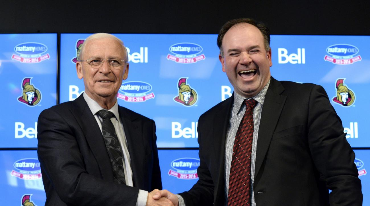 Ottawa Senators former general manager Bryan Murray, left, shakes hands with incoming general manager Pierre Dorion, right, following a press conference in Ottawa, Sunday, April 10, 2016.  Bryan Murray is stepping down as Ottawa Senators general manager a