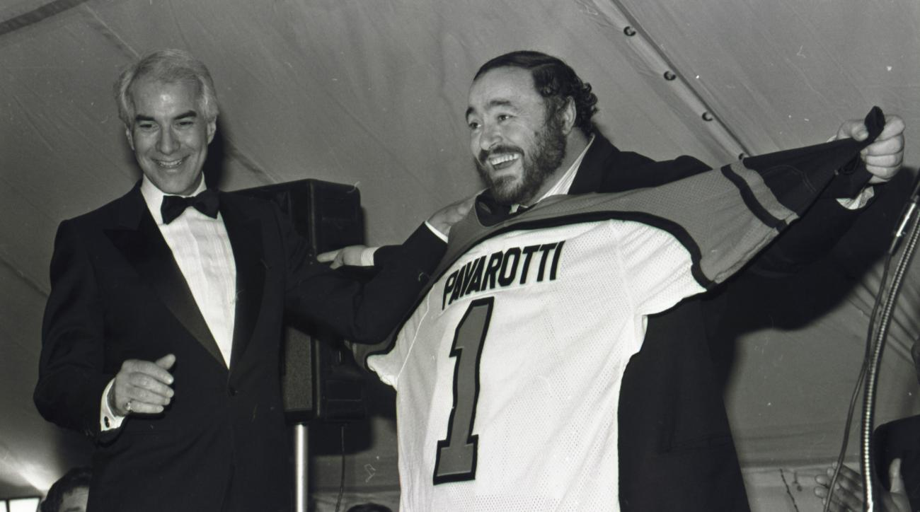 FILE - In this March 15, 1985 file photo, tenor Luciano Pavarotti shows off the Philadelphia Flyers jersey presented to him by Flyers owner Ed Snider, left, after a concert by Pavarotti at the Spectrum in Philadelphia. Ed Snider, the Philadelphia Flyers f
