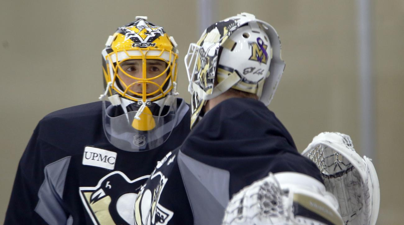 Pittsburgh Penguins goalie Marc-Andre Fleury, who has been out of action with concussion symptoms, talks with goalie Jeff Zatkoff during a practice session for the NHL hockey playoffs against the New York Rangers, Monday, April 11, 2016, at their practice