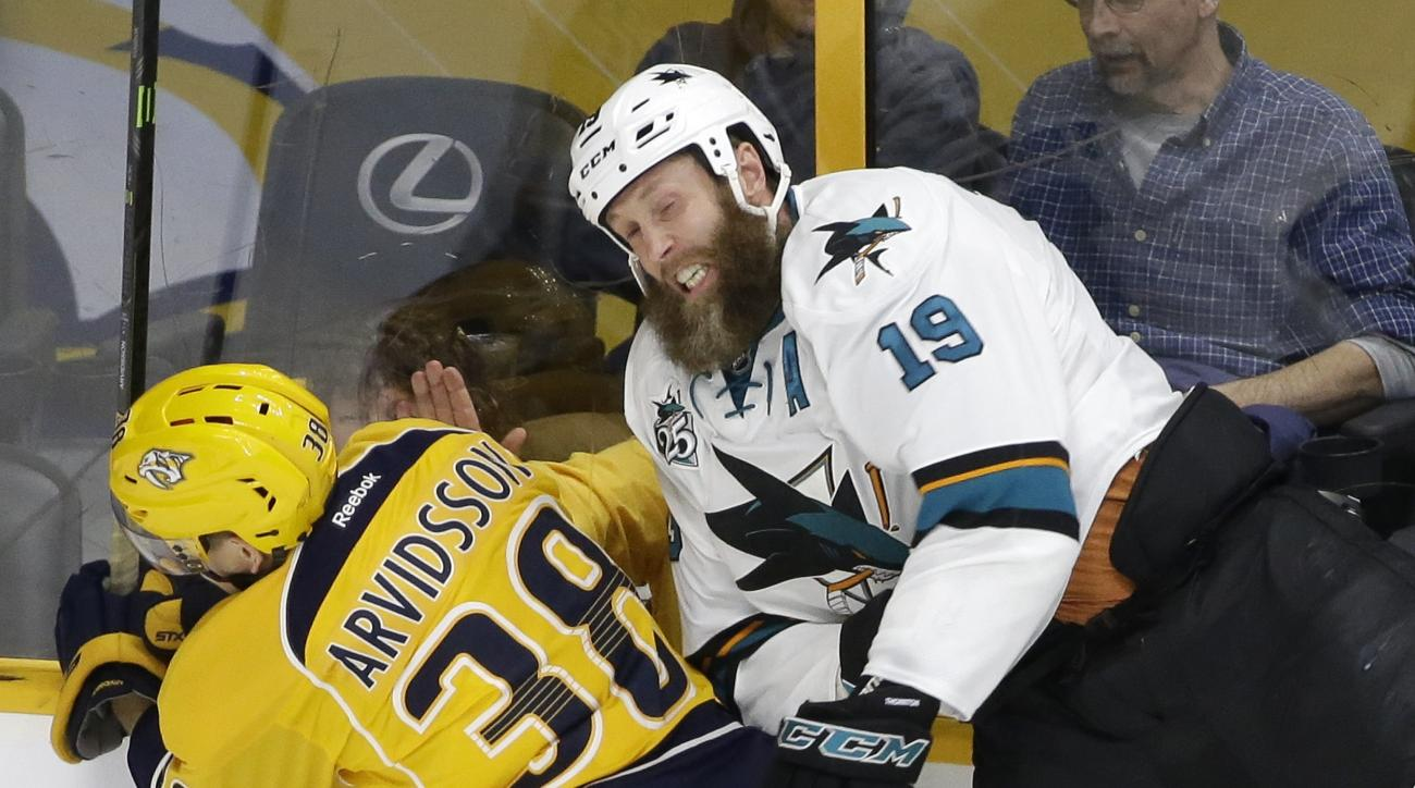 FILE - In this April 2, 2016 file photo, San Jose Sharks center Joe Thornton (19) and Nashville Predators forward Viktor Arvidsson (38), of Sweden, hit the glass as they chase the puck during the first period of an NHL hockey game in Nashville, Tenn. Thor