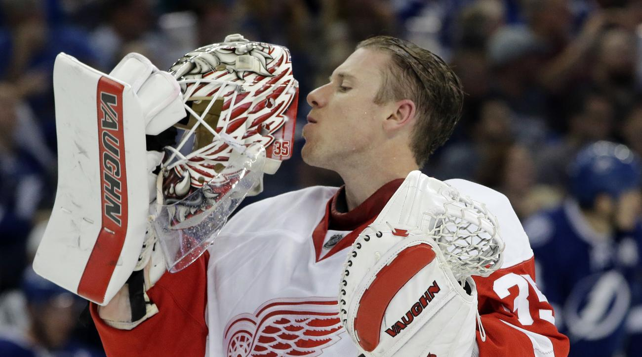 Detroit Red Wings goalie Jimmy Howard (35) kisses his face mask during a break in the second period of Game 1 in a first-round NHL hockey Stanley Cup playoff series against the Tampa Bay Lightning on Wednesday, April 13, 2016, in Tampa, Fla. (AP Photo/Chr