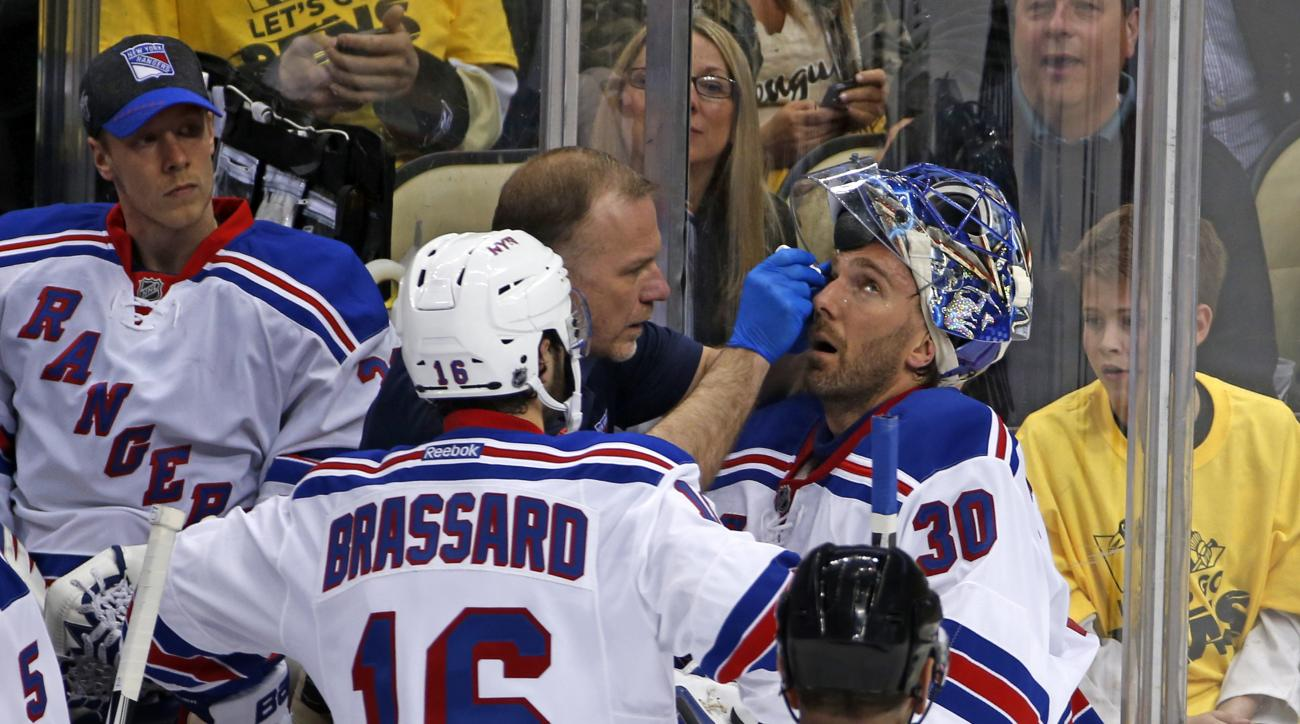 New York Rangers goalie Henrik Lundqvist (30) is attended to by a trainer after getting a stick to the face during the first period of a first-round NHL playoff hockey game against the Pittsburgh Penguins in Pittsburgh, Wednesday, April 13, 2016. Lundqvis