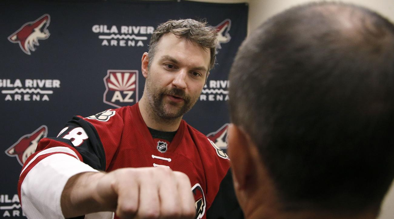 In this photo taken on Tuesday, Nov. 24, 2015, Arizona Coyotes' John Scott, left, gives Associated Press sports writer John Marshall, right, a hockey fighting tutorial, in Glendale, Ariz. The Coyotes traded Scott in January, 2016. (AP Photo/Ross D. Frankl