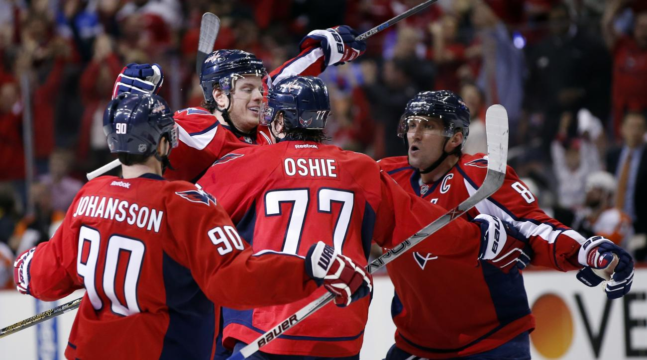 Washington Capitals center Marcus Johansson (90), from Sweden, right wing T.J. Oshie (77) and left wing Alex Ovechkin (8), from Russia, celebrate with defenseman John Carlson, second from left, after his goal against the Philadelphia Flyers during the sec