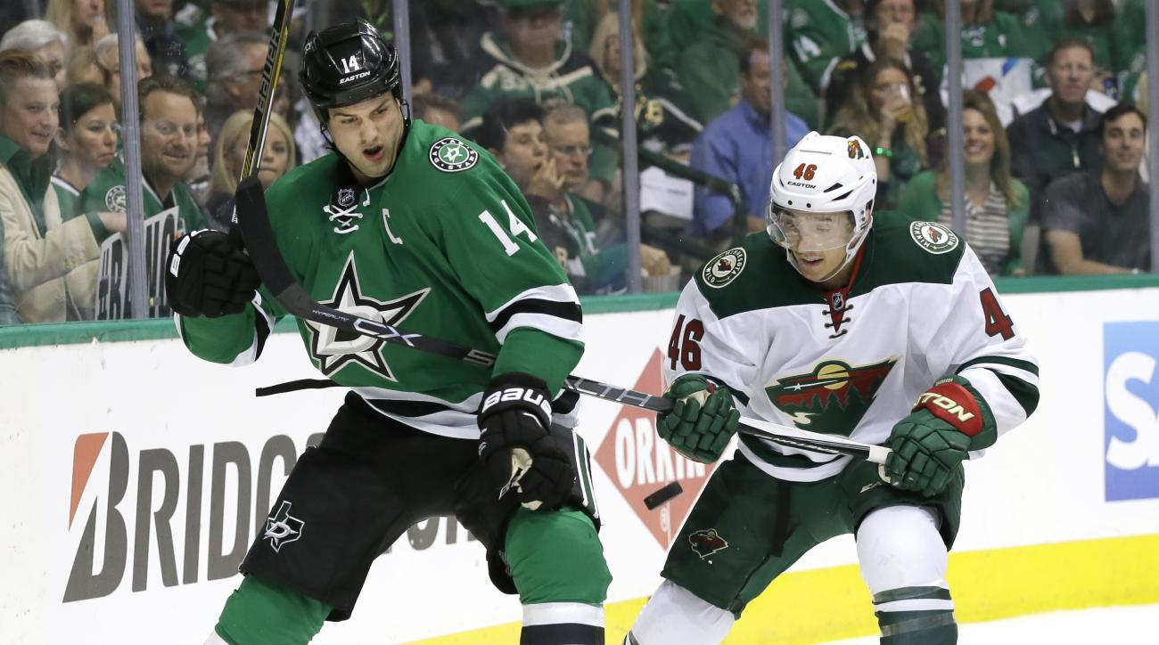 Minnesota Wild defenseman Jared Spurgeon (46) and Dallas Stars left wing Jamie Benn (14) skate for the puck during the first period of Game 1 in a first-round NHL hockey Stanley Cup playoff series Thursday, April 14, 2016, in Dallas. (AP Photo/LM Otero)