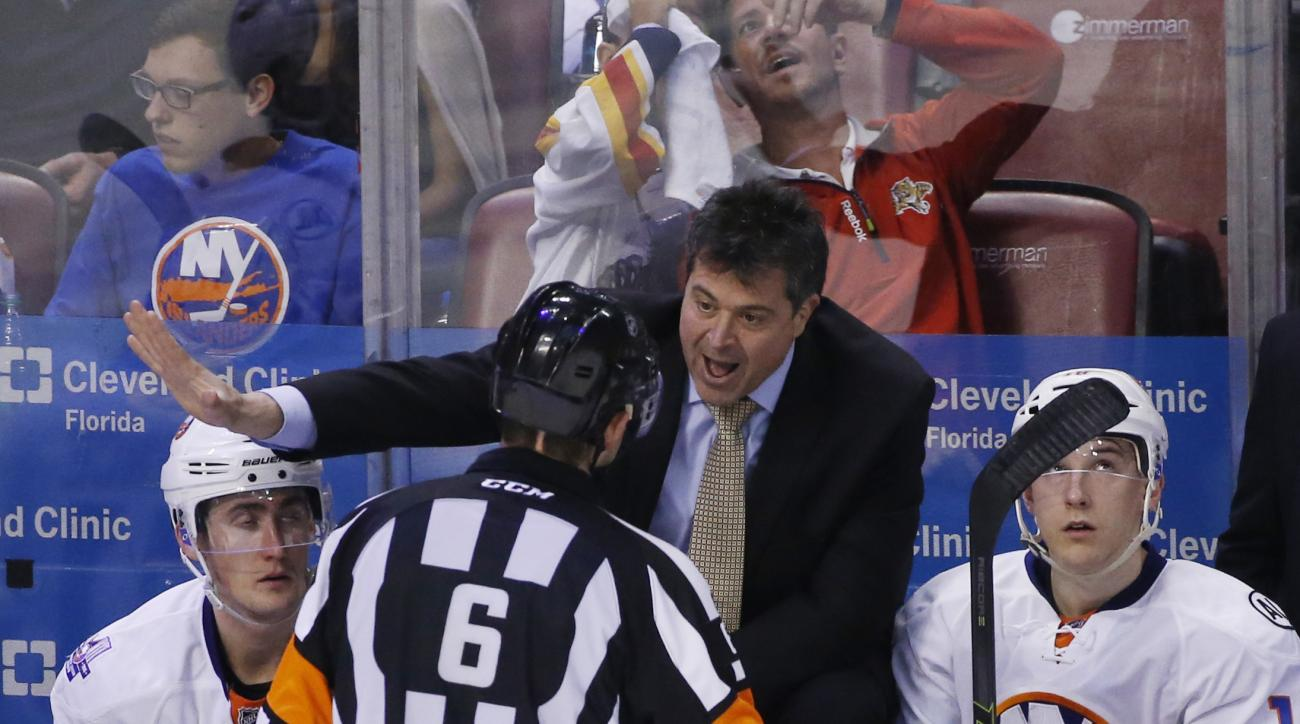 New York Islanders head coach Jack Capuano talks with referee Francis Charron (6) during the second period of Game 2 in a first-round NHL hockey Stanley Cup playoff series against the Florida Panthers, Friday, April 15, 2016, in Sunrise, Fla. (AP Photo/Wi