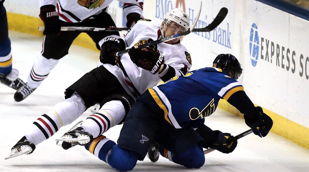 St. Louis Blues Paul Stastny and Chicago Blackhawks Tomas Fleischmann look to control the puck during the third period of Game 2 of a first-round series in the NHL hockey Stanley Cup playoffs, Friday, April 15, 2016, in St. Louis. The Blackhawks won 3-2 t