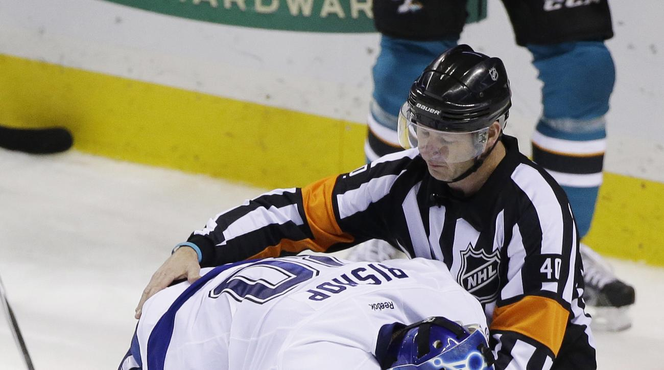 FILE - In this Dec. 5, 2015, file photo, Tampa Bay Lightning goalie Ben Bishop is assisted by referee Steve Kozari after being injured during the third period of an NHL hockey game against the San Jose Sharks in San Jose, Calif. Even after taking an accid