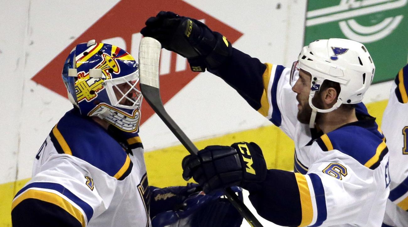 St. Louis Blues goalie Brian Elliott, left, celebrates with defenseman Joel Edmundson after the Blues defeated the Chicago Blackhawks 4-3 in Game 4 of an NHL hockey first-round Stanley Cup playoff series Tuesday, April 19, 2016, in Chicago. (AP Photo/Nam