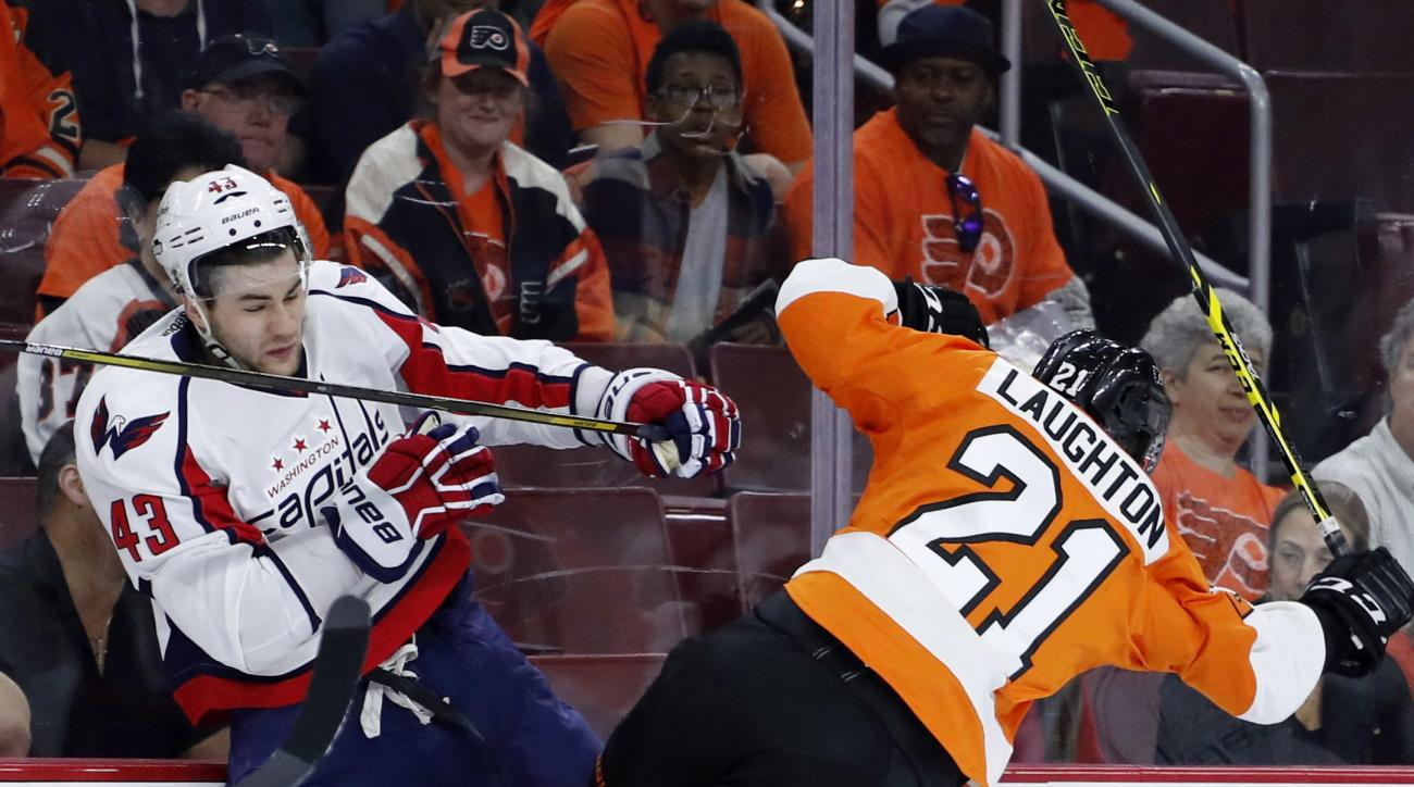 Washington Capitals' Tom Wilson, left, and Philadelphia Flyers' Scott Laughton collide during the first period of Game 4 in the first round of the NHL Stanley Cup hockey playoffs, Wednesday, April 20, 2016, in Philadelphia. (AP Photo/Matt Slocum)