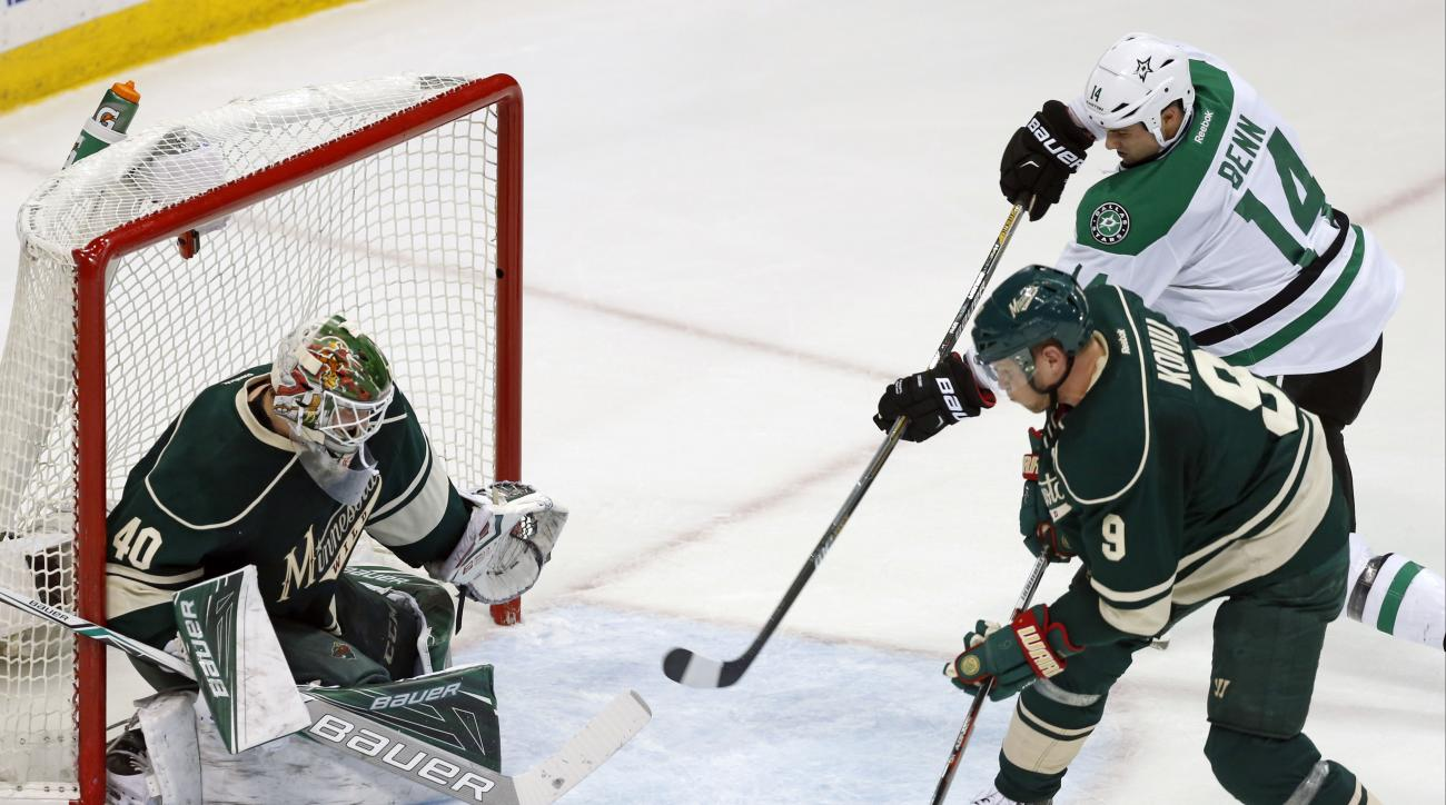 Dallas Stars' Jamie Benn, top right, looks for the pass as Minnesota Wild's Mikko Koivu of Finland and goalie Devan Dubnyk, left, defend during the first period of Game 4 in the first round of the NHL Stanley Cup hockey playoffs Wednesday, April 20, 2016,