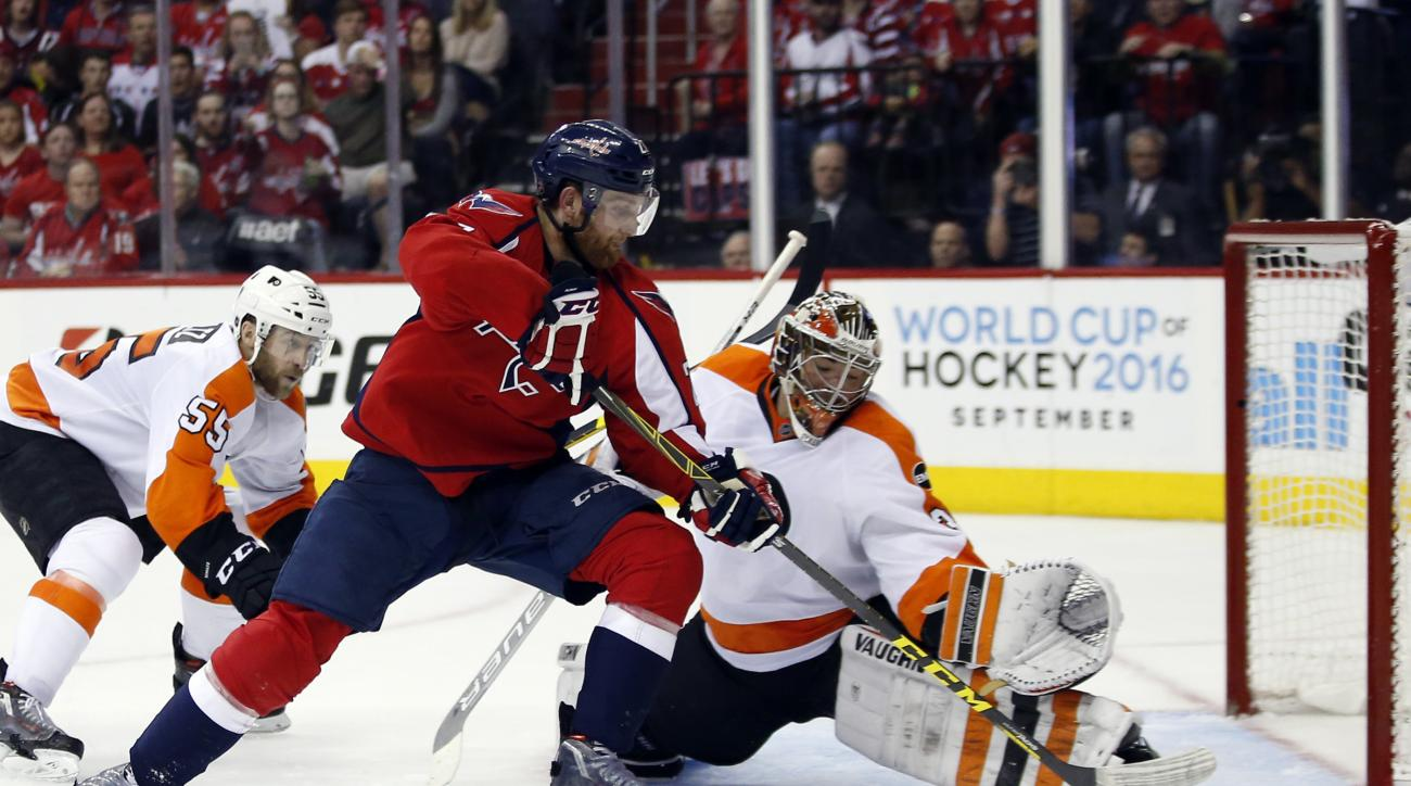 Washington Capitals defenseman Karl Alzner (27) can't score past Philadelphia Flyers goalie Michal Neuvirth (30), from the Czech Republic, during the second period of Game 5 in a first-round NHL Stanley Cup hockey playoff series, Friday, April 22, 2016, i