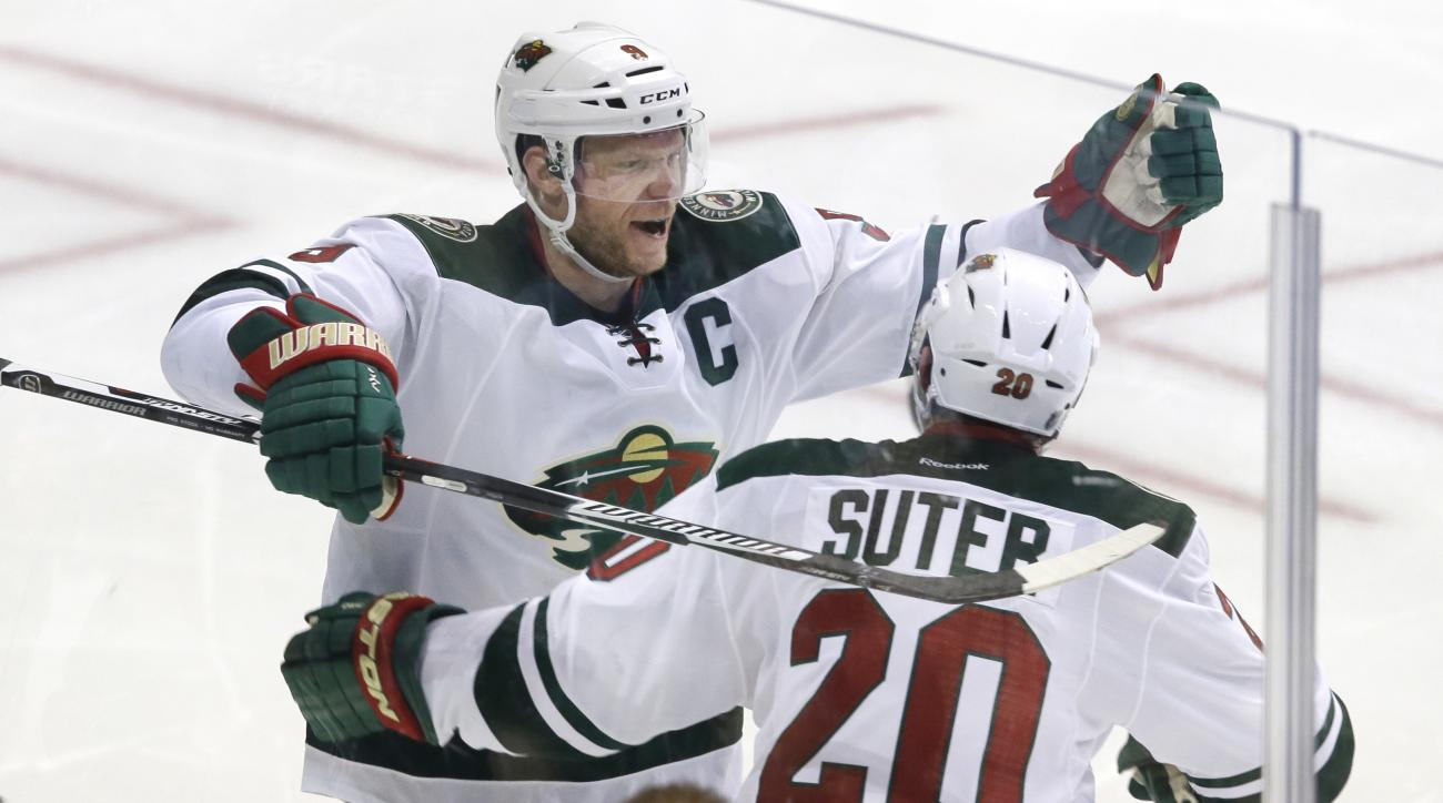 Minnesota Wild center Mikko Koivu (9) celebrates his goal with defenseman Ryan Suter (20) during overtime in Game 5 in the first round of the NHL Stanley Cup playoffs against the Dallas Stars on Friday, April 22, 2016, in Dallas. The Wild won 5-4. (AP Pho