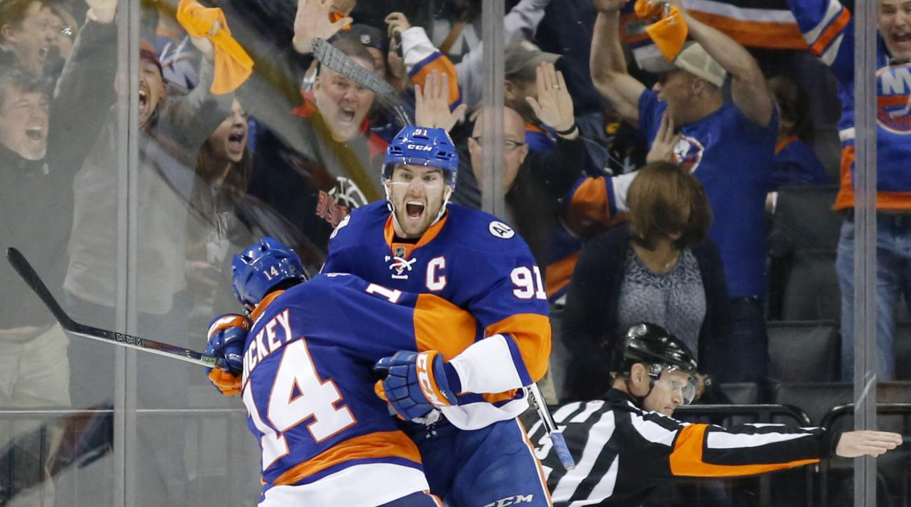 New York Islanders defenseman Thomas Hickey (14) leaps in the air with New York Islanders center John Tavares (91) after Tavares scored the winning goal in the second overtime period of Game 6 of an NHL hockey first-round Stanley Cup playoff series agains