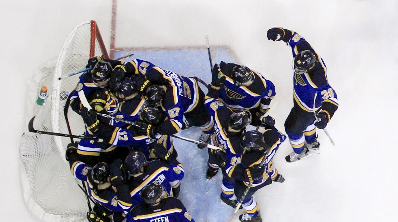 CORRECTS FINAL SCORE TO 3-2 INSTEAD OF 4-3 - Members of the St. Louis Blues gather around goalie Brian Elliott following the Blues' 3-2 victory over the Chicago Blackhawks in Game 7 of an NHL hockey first-round Stanley Cup playoff series Monday, April 25,