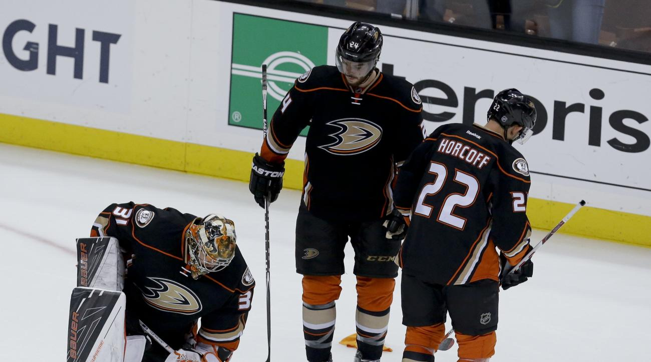 Anaheim Ducks goalie Frederik Andersen, left, reacts after the Ducks' 2-1 loss to the Nashville Predators as Shawn Horcoff, right, and Simon Despres stand nearby after Game 7 of an NHL hockey Stanley Cup playoffs first-round series in Anaheim, Calif., Wed