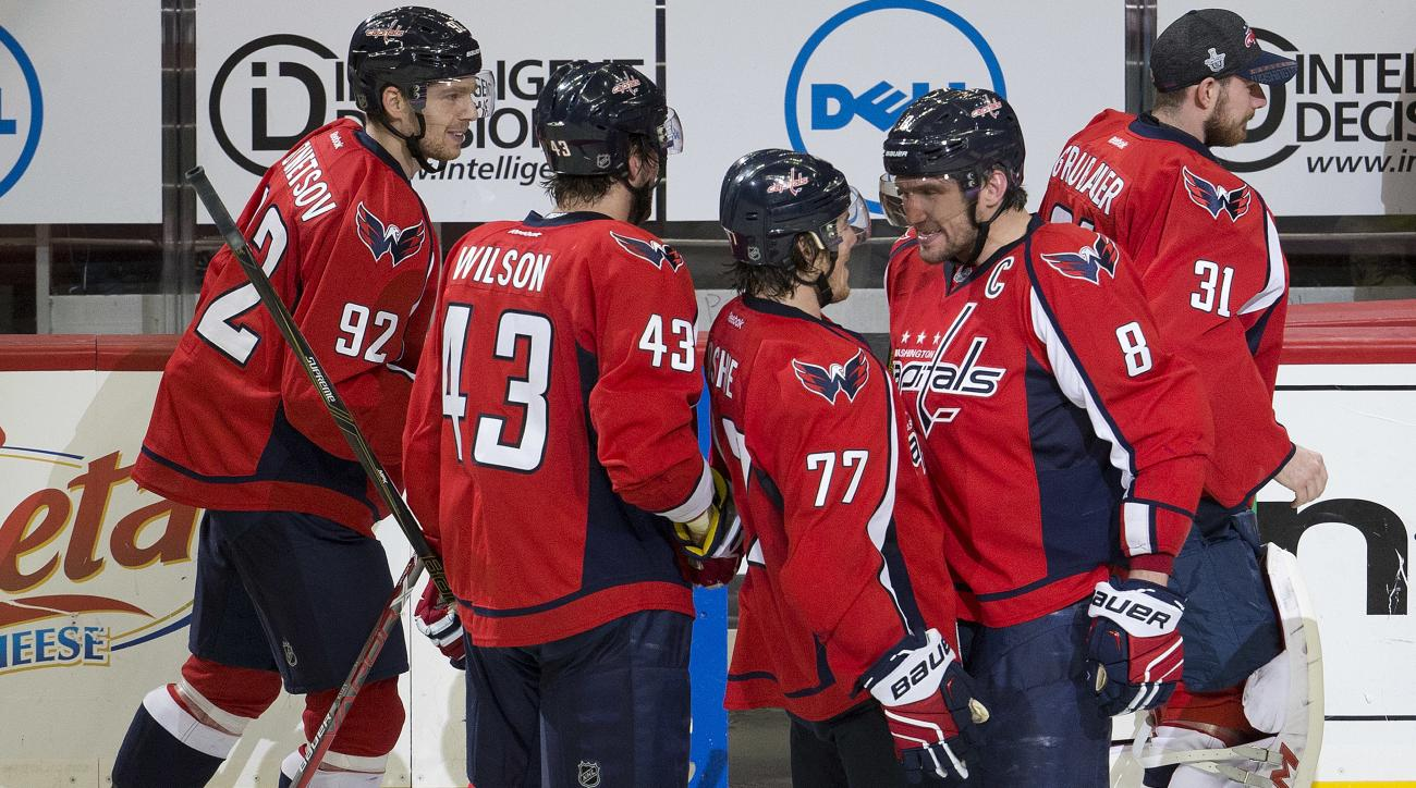 Washington Capitals right wing T.J. Oshie (77) is congratulated by teammate Alex Ovechkin (8) as they celebrate Oshie's overtime goal against the Pittsburgh Penguins to end Game 1 of an NHL hockey Stanley Cup Eastern Conference semifinal, Thursday, April
