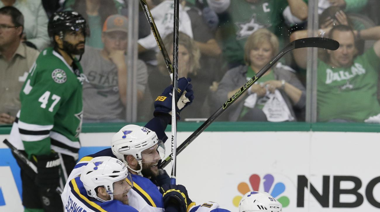 St. Louis Blues center David Backes (42) celebrates his goal with teammates Jaden Schwartz (17) and Vladimir Tarasenko (91) as Dallas Stars defenseman Johnny Oduya (47) skates by during overtime of Game 2 of the NHL hockey Stanley Cup Western Conference s