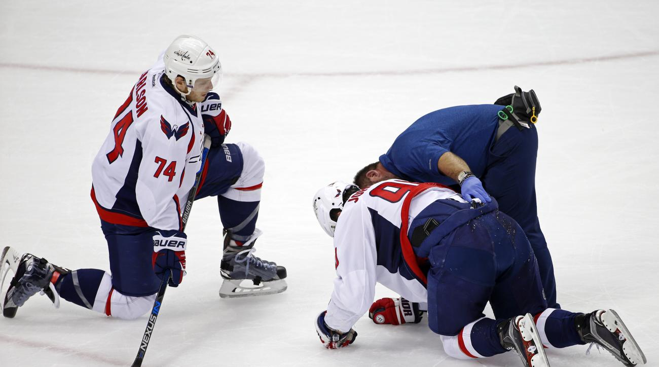 Washington Capitals' Marcus Johansson (90) is helped by a trainer as John Carlson (74) watches during the first period of Game 3 in an NHL hockey Stanley Cup Eastern Conference semifinals in Pittsburgh, Monday, May 2, 2016. (AP Photo/Gene J. Puskar)