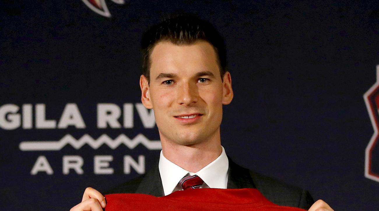 Newly appointed Arizona Coyotes general manager John Chayka holds a game jersey after a news conference announcing his promotion, Thursday, May 5, 2016, in Glendale, Ariz. Chayka is the youngest GM in NHL history. (AP Photo/Matt York)
