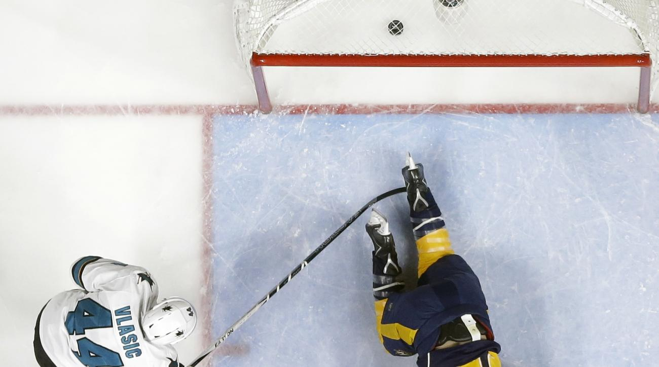Nashville Predators center Colin Wilson (33) slides across the crease after scoring a goal against San Jose Sharks goalie Martin Jones (31) and defenseman Marc-Edouard Vlasic (44) during the first period in Game 4 of an NHL hockey Stanley Cup Western Conf