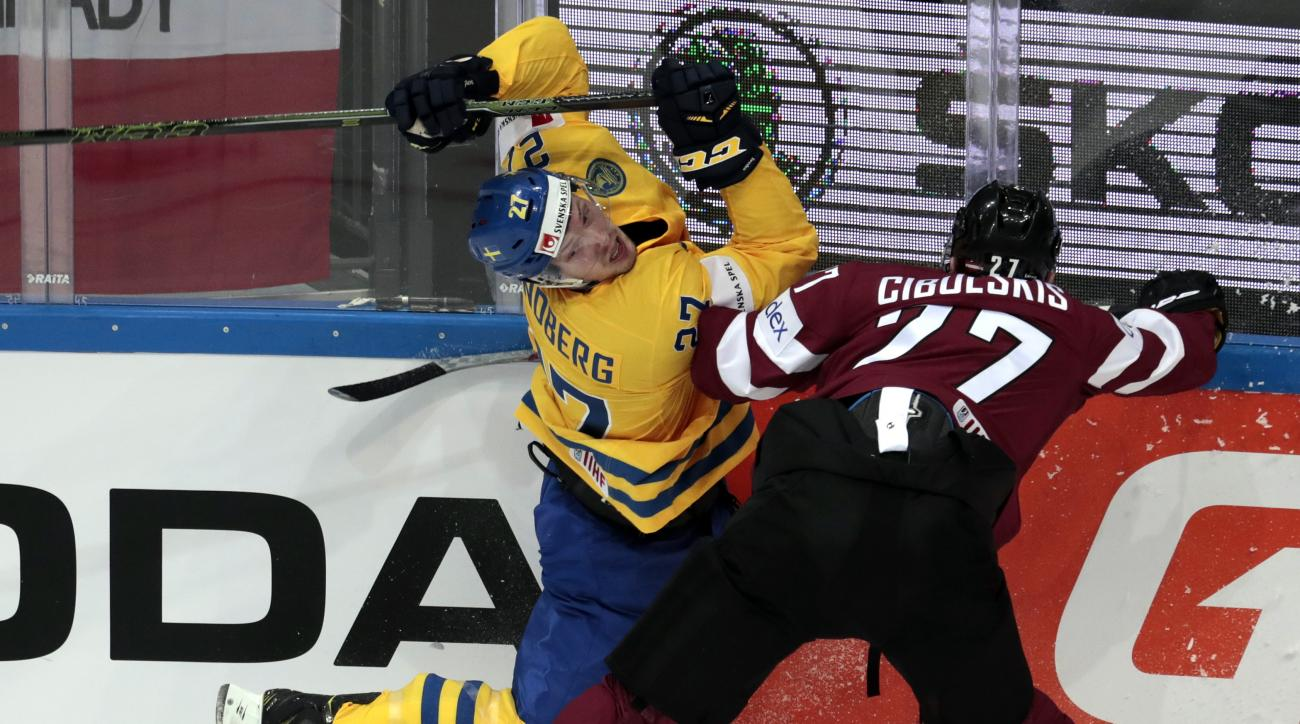 Latvia's Oskars  Cibulskis, right, tackles Sweden's Martin Lundberg during the Hockey World Championships Group A match in Moscow, Russia, on Friday, May 6, 2016. (AP Photo/Ivan Sekretarev)