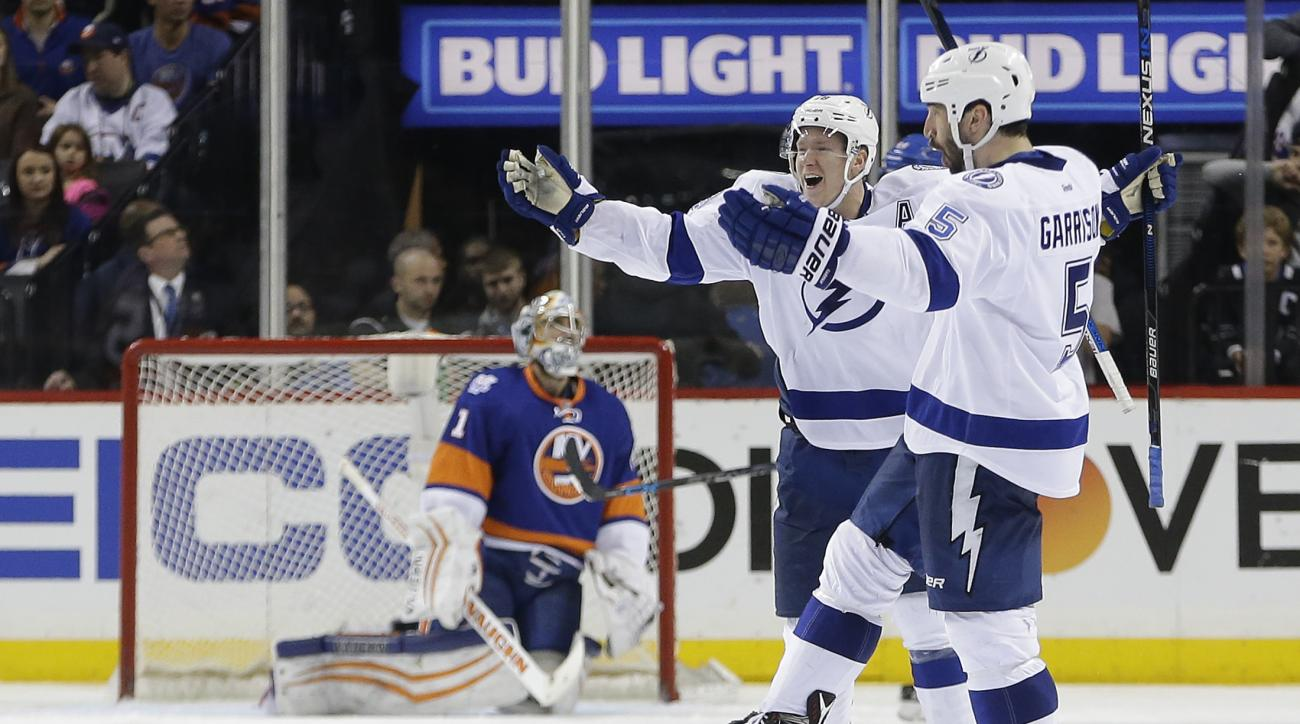 Tampa Bay Lightning defenseman Jason Garrison (5) and left wing Ondrej Palat (18) celebrate after Garrison scored the winning-goal in overtime against New York Islanders goalie Thomas Greiss (1) during the overtime period of Game 4 of the NHL hockey Stanl