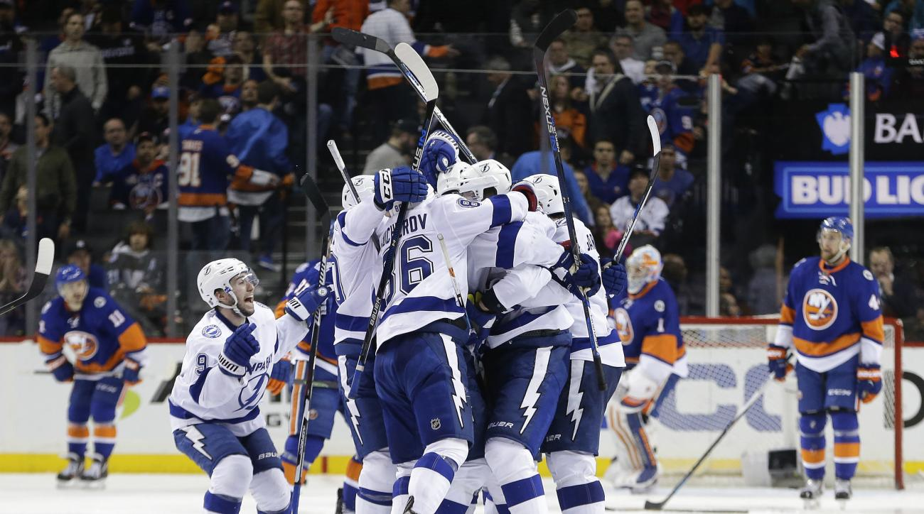 The Tampa Bay Lightning celebrate the game winning goal by defenseman Jason Garrison (5) against the New York Islanders during the overtime period of Game 4 of the NHL hockey Stanley Cup Eastern Conference semifinals, Friday, May 6, 2016, in New York. The