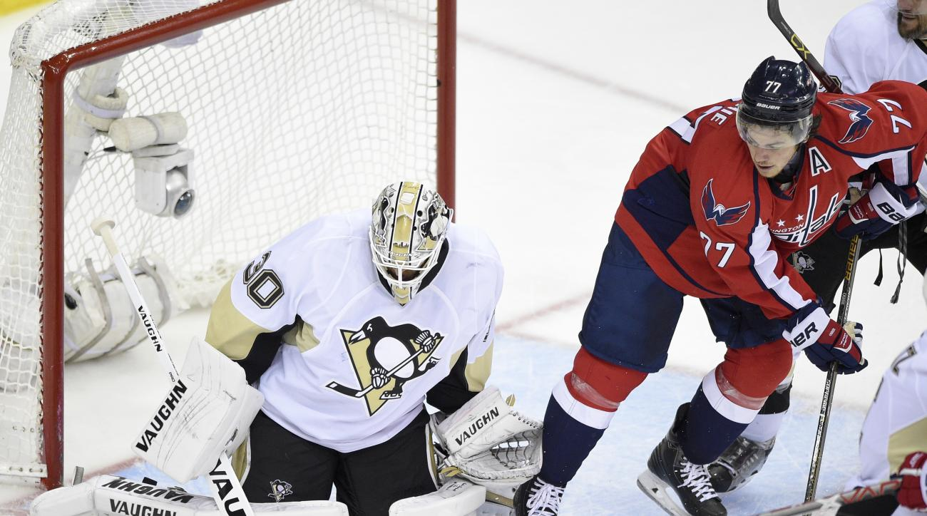 Pittsburgh Penguins goalie Matt Murray (30) stops the puck as Washington Capitals right wing T.J. Oshie (77) looks on during the third period of Game 5 in an NHL hockey Stanley Cup Eastern Conference semifinals, Saturday, May 7, 2016, in Washington. The C