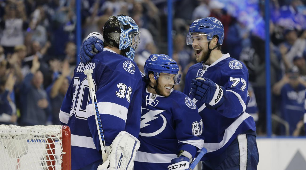 Tampa Bay Lightning's goalie Ben Bishop (30) is congratulated by Jonathan Marchessault (81) and Victor Hedman (77), of Sweden, at the end of the third period of Game 5 of the NHL hockey Stanley Cup Eastern Conference semifinals against the New York Island