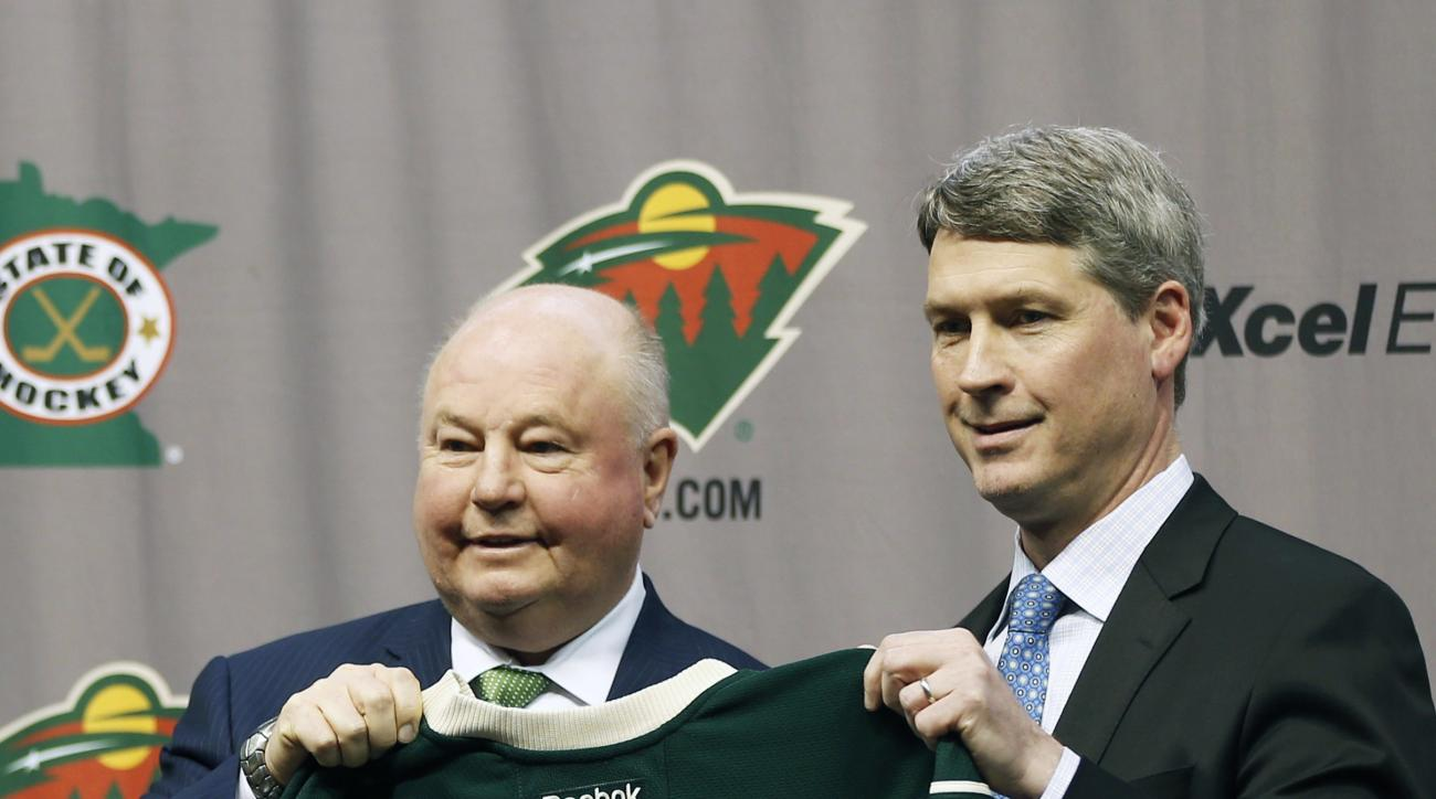 Bruce Boudreau, left, is introduced by Minnesota Wild general manager Chuck Fletcher as the new Wild NHL hockey team head coach during a news conference by the NHL hockey team Tuesday, May 10, 2016, in St. Paul, Minn. (AP Photo/Jim Mone)