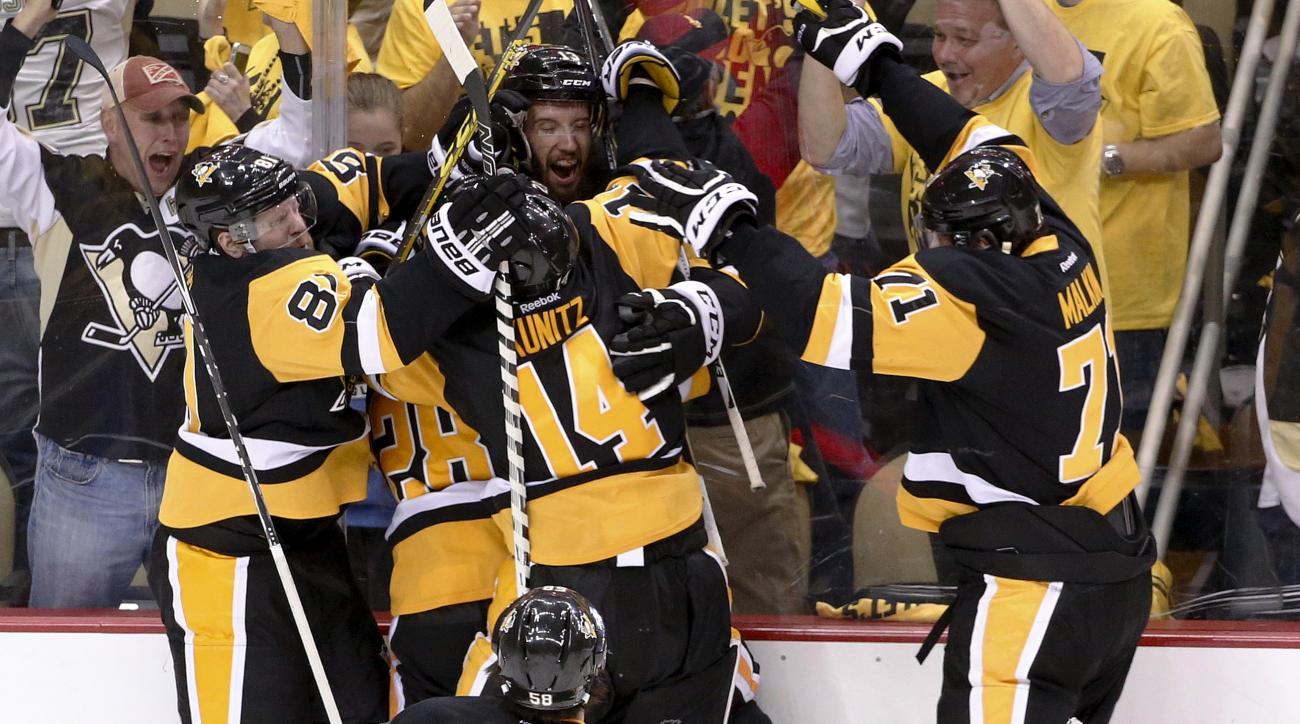 Pittsburgh Penguins' Nick Bonino, facing camera at top, is mobbed by teammates after scoring against the Washington Capitals during overtime of Game 6 of the NHL hockey Stanley Cup Eastern Conference semifinals, Tuesday, May 10, 2016 in Pittsburgh. The Pe