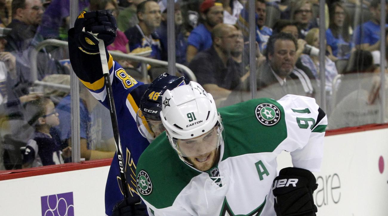 FILE - In this Sept. 27, 2014, file photo, St. Louis Blues defenseman Petteri Lindbohm (48) and Dallas Stars center Tyler Seguin (91) battle for control of the puck in the second period of a preseason NHL hockey game in Kansas City, Mo. Seguin missed the