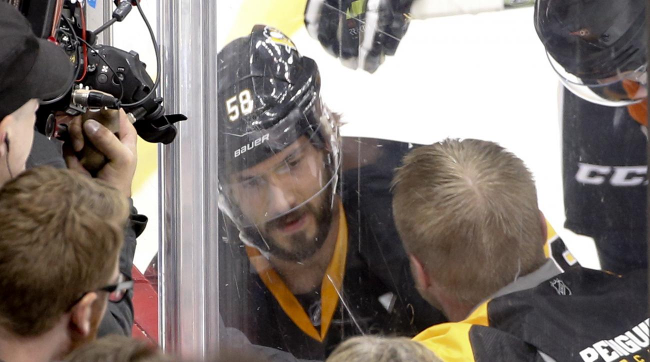 Pittsburgh Penguins' Kris Letang (58) is seen through the glass as he is checked by a trainer during the first period of Game 1 of the NHL hockey Stanley Cup Eastern Conference finals against the Tampa Bay Lightning Friday, May 13, 2016, in Pittsburgh. Le